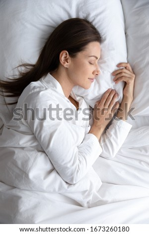 Top above view vertical image tranquil young brunette woman in pajamas lying under duvet on comfortable orthopedic mattress, sleeping on soft pillow, enjoying sweet dreams good night rest in bed.