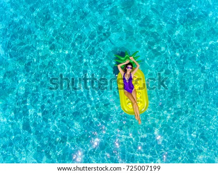 Top aerial view of a woman swimming with inflatable mattress in a pineapple shape. On holidays having fun and relaxing at the beach.