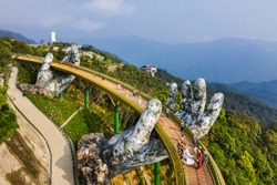Top aerial view of the famous Golden Bridge is lifted by two giant hands in the tourist resort on Ba Na Hill in Da Nang, Vietnam.