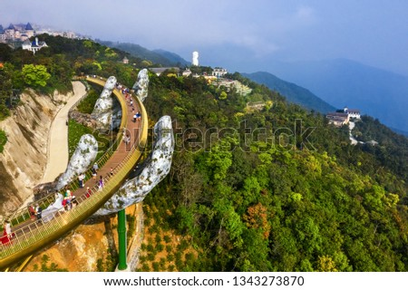 """Top aerial view of the famous Golden Bridge is lifted by two giant hands in the tourist resort on Ba Na Hill in Da Nang, Vietnam. """" Cau Vang"""" is a favorite destination for tourists"""