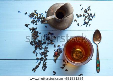 top aerial view on bright blue desk with glass of tea, jug, tea leaves and teaspoon on blue vivid table