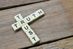 Top angle view of aphabet letters with text TRUST and TRUTH over wooden background.