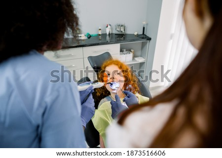 Top angle view of little girl patient having dental treatment at dentist's office. Team of two multiethnic female dentists providing tooth restoration with filling with curing polymerization UV lamp