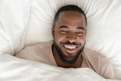 Top close up view laughs handsome african guy lying in bed woke up feel peppy and healthy sleeping enough hours. Under white warm blanket on fresh soft sheets comfortable mattress resting cheerful man
