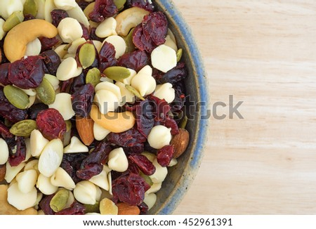 Top close view of a bowl full of an assortment of nuts and dried cranberries trail mix on a wood table top. #452961391