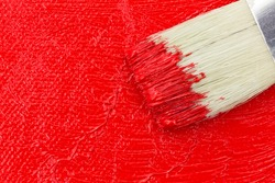 Top close view of wet red paint on an artist canvas with a brush.