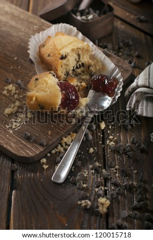 Top closeup view of broken cupcake and iron spoon with jam and scattered chocolate drops make in the dark tonality.