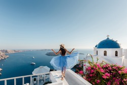 Top destination in Europe, Santorini, Greece. Beautiful woman enojing view on Santorini Island, Cyclades, Greece