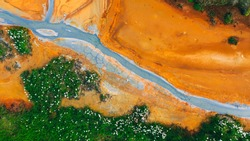 Top down aerial view from drone on geothermal icelandic area in Iceland Seltun near Krysuvik and Kleifarvant lake, blue water and orange colorful ground texture structure hot spring and mud background