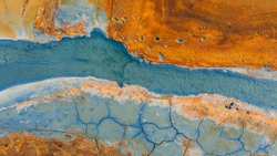 Top down aerial view from drone on geothermal icelandic in Iceland Seltun  Krysuvik Kleifarvant lake blue water and orange ground texture structure hot spring mud background foot prints animals birds