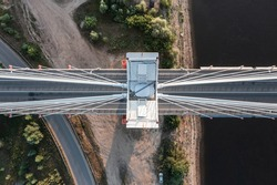 Top down aerial view of a pillar of white suspension bridge standing on a river bank