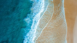Top down aerial view of beach with waves crashing into the sand during day time