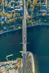 Top down aerial view of the vehicle bridge over the river. Drone photography. Cars on the road. City view.