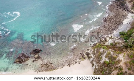 Top-down drone shot of an idyllic Koka Beach. Hidden gem of Flores Indonesia. Beauty in the nature. Calm waves washing the cliff's slopes. Serenity and calmness. There are a lot of boulders in the sea