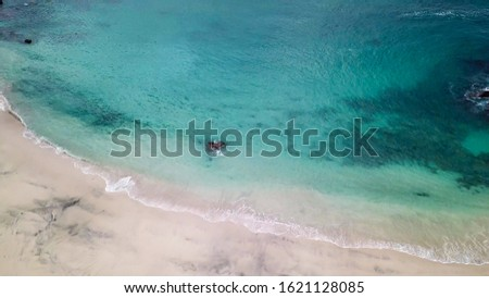Top-down drone shot of an idyllic Koka Beach. Hidden gem of Flores Indonesia. Beauty in the nature. Calm waves washing the sandy shore gently. Serenity and calmness. There are some boulders in the sea