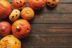 Top-down flat lay shot of ripe orange pumpkins carved for Halloween lying on brown wooden table, copy space