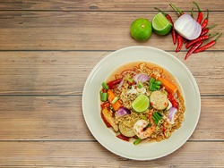 Top-down instant noodle spicy salad with seafood, Thai noodle spicy mixed seafood salad. Thai cuisine delicious food popular (Yum Mama)