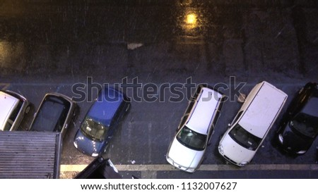 Top down picture of city streets at night and heavy rainfall and thunderstorm flashes illuminating the streets and parked cars for short period of time typical city scene during rain season