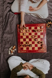 Top-down portrait on two people playing chess on fancy old red yellow chess board. Two people in white Arabic dress sitting with crossed legs on  brown silky blanket. Board games. Smart time spending