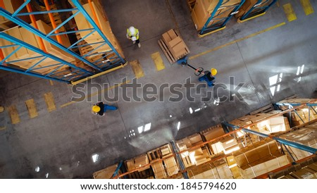 Top-Down View: In Warehouse People Working, Forklift Truck Operator Lifts Pallet with Cardboard Box. Logistics, Distribution Center with Products Ready for Global Shipment, Customer Delivery Stockfoto ©