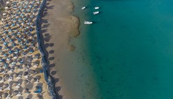Top down view of a beach with tourists suntbeds and umbrellas with sand beach and clear blue water in egypt