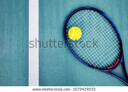 Top down view of a tennis racket, a single ball and the white line on a cyan concrete tennis court