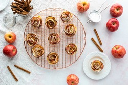 Top down view of apple rose pastries on a rose gold cooling rack with one pastry on a plate ready for eating.