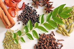 Top down view of assorted Spices of Kerala. Cinnamon, pepper, clove, star anise, cumin, cardamom, nutmeg and curry leaves form integral ingredients of Kerala cuisine.