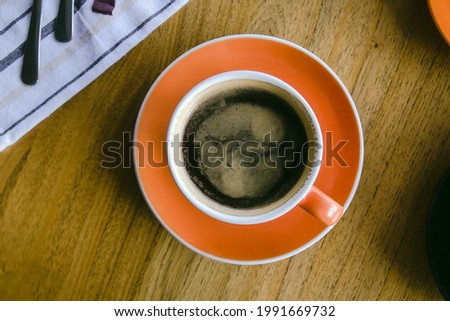 Top down view of black coffee on a wood table