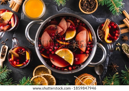 Top-down view of cooking pot of hot wine with aromatic spices on a black textured background. Christmas mulled wine. New Year's warming drink. Stockfoto ©