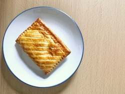 Top down view of flakey golden brown baked pasty on white plate on wooden table