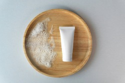 Top down view of organic gentle facial skincare product cleanser white tube with soap bubbles and blank label on bamboo wooden plate grey blue cardboard box paper background.