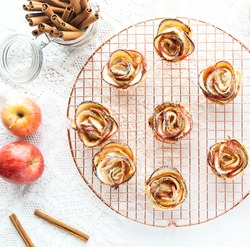 Top down view of pastry apple roses on a rose gold coloured cooling rack.