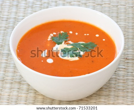 Top down view of red tomato soup in white bowl, sprinkled with cream