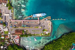 Top down view of the Padang Bai harbor in Bali, Indonesia, where trucks get out of a roro car ferry coming from Lombok