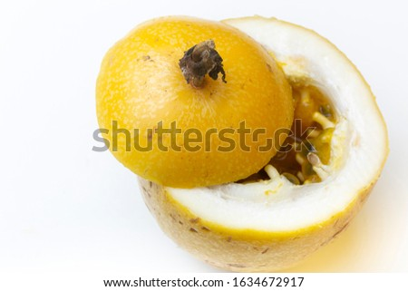 Top down view of yellow Passion fruit on a white surface opened up with the inside juicy pulp visible