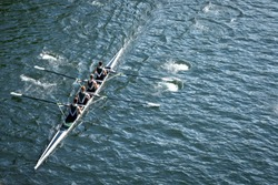 Top down view on a four person crew team, racing a rowing shell on a calm blue lake, with space for text on right