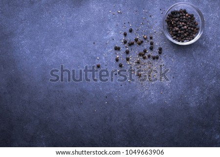 Top down view on a glass dish of whole black peppercorns in top right corner, beside spilled seeds and freshly cracked pepper, on a slate background #1049663906