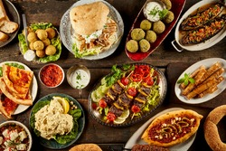 Top down view on freshly prepared delicious varieties of Mediterranean dishes with bread on wooden table