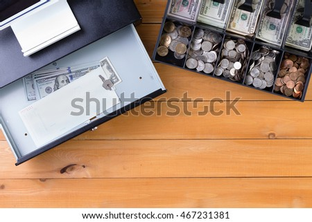 Top down view on separate cash drawer stocked with coins and American dollars beside open register with key and large denomination bills on wooden table. Includes copy space.