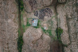 Top-down view over the textured Irish landscape and abandoned building.Marram-grass-anchored dunes at North Bull Island, Dublin, Ireland.