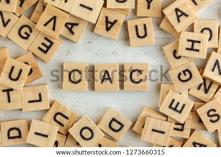 Top down view, pile of square wooden blocks with letters CAC (stands for Customer acquisition cost) on white board.