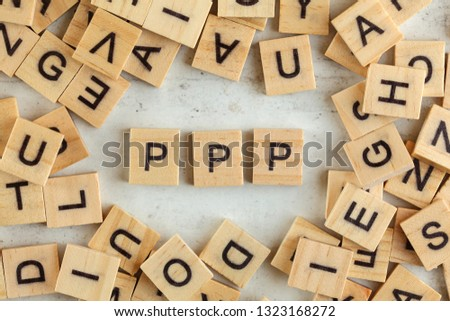Top down view, pile of square wooden blocks with letters PPP (stands for Praise, Picture, Push) on white board.