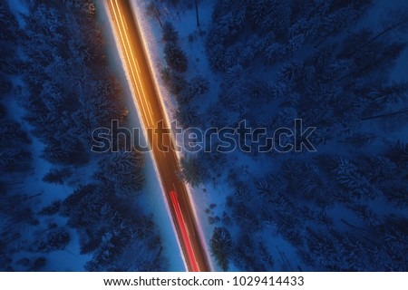 Top down view to road in the snowy wood. Romantic night aerial photo of cars traveling on the mountain road.