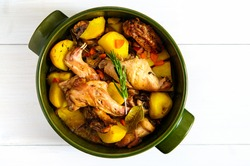 Top flat view of roasted rabbit meat with vegetables and herbs  in round ceramic pot on white wooden table surface, copy space