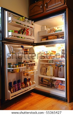Top freezer kitchen refrigerator with doors open and shelves full of groceries with fresh and frozen food and cold bottles