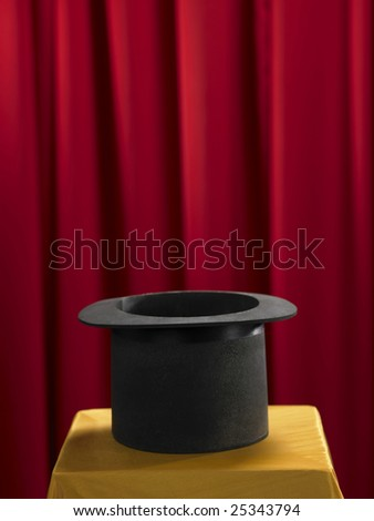 top hat on the stage with red curtain