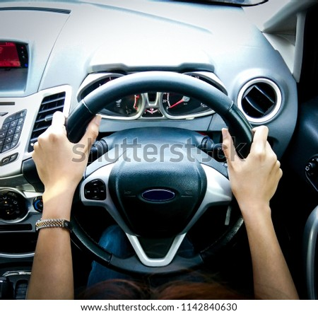 Top interior view of two female hands are catching on the steering wheel to drive the car.