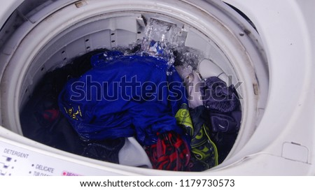 Top load washing machine with clothes loaded to be cleaned #1179730573