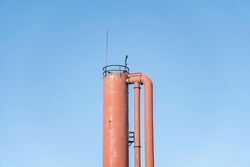 Top of a cylinder tower with pipes against a clear blue sky at Tacoma, Washington